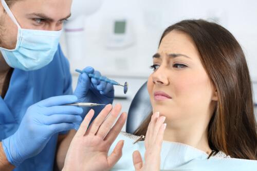 En kvinde sidder i en tandlægestol og virker utilpas overfor situationen