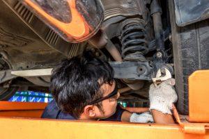 En man reparerer støddæmpere på en bil