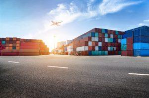 En industrihavn fyldt med containere og et flyv der flyver over industrihavnen i solskin