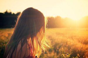 En kvinde står ved en kornmark og kigger mod solnedgangen