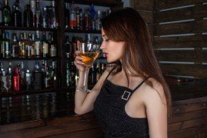 En kvinde står med en cocktail i hånden på en bar